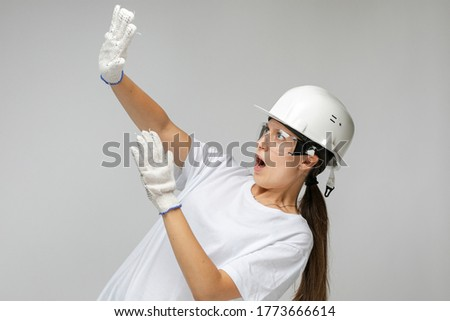 Smiling confident woman architect in a construction helmet on a light background