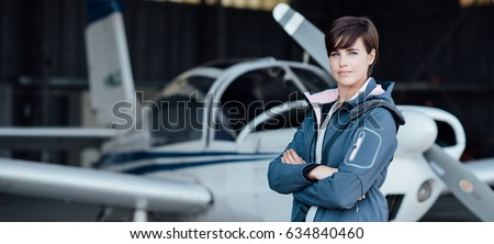 Smiling confident woman posing with her airplane in the hangar before departure, aviation and light aircrafts concept