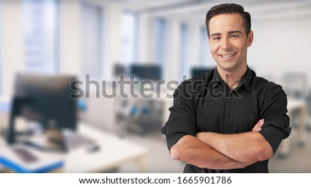 Smiling confident young businessman standing with folded hands