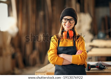 Smiling confident young female joiner in apron standing near workbench and looking at camera friendly while working in craft workshop Сток-фото ©