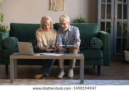 Smiling contemporary senior couple spouses use laptop new technologies paying banking bills online, happy modern mature husband and wife calculate finances, manage domestic expenditures at home