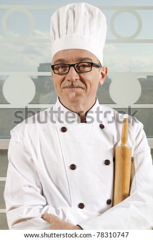 Smiling cook with white hat having pin roll in hand - stock photo