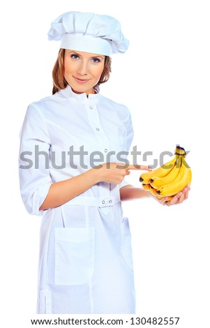 Smiling cook woman holding fresh banana. Isolated over white background.