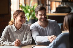 Smiling couple at meeting, husband shaking hand of broker, financial advisor or agent in cafe, making successful deal, taking loan or mortgage, purchasing real estate, signing contract