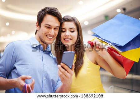 Smiling couple checking something on the mobile phone