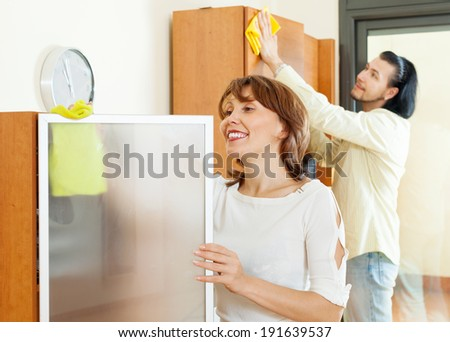 Smiling couple cleaning wooden furiture with rag at home