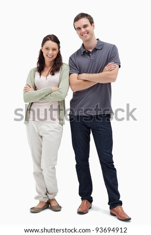 Smiling couple crossing their arms against white background