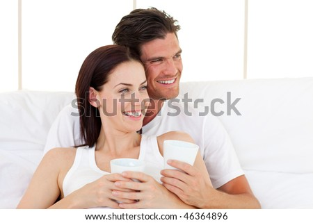 Smiling couple drinking coffee lying in the bed
