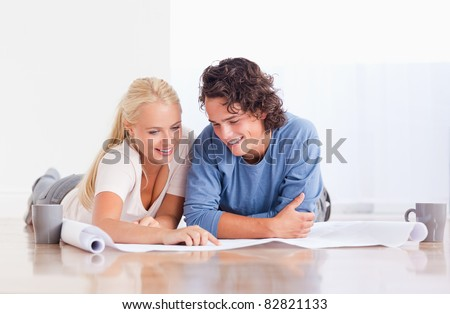 Smiling couple getting ready to move in a new house while lying on the floor - stock photo