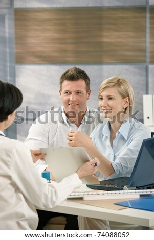 Smiling couple getting result from medical doctor in office.