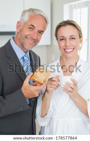 Smiling couple having breakfast in the morning before work at home in the kitchen
