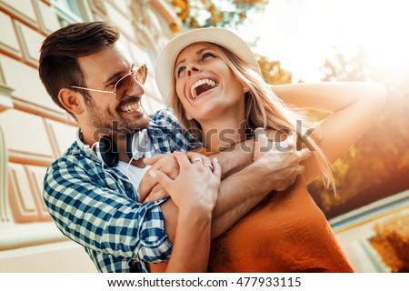 Smiling couple in love outdoors.Young happy couple hugging on the city street. #477933115