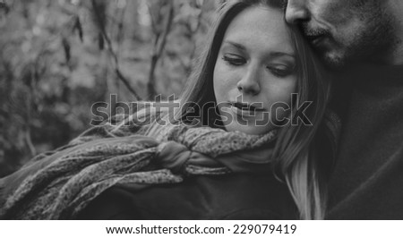 Smiling couple in love rests in park, man embraces a woman. Black and white image