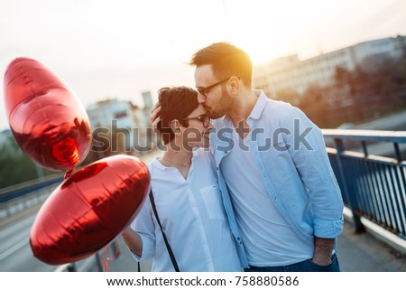 smiling couple in love with balloons on sunset