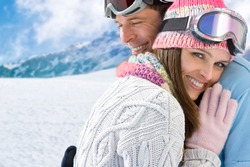Smiling couple in ski-wear hugging each other on a cold sunny day at a ski resort in the mountains with copy space.