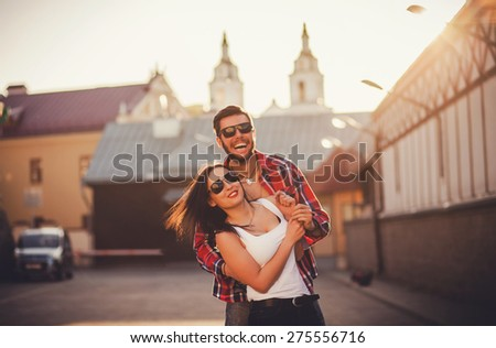 smiling couple in sunglasses having fun in city. love and friendship.