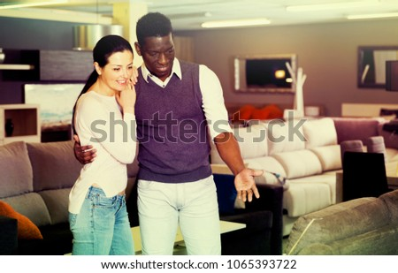 Smiling couple is choosing new furniture for interior their room in the store