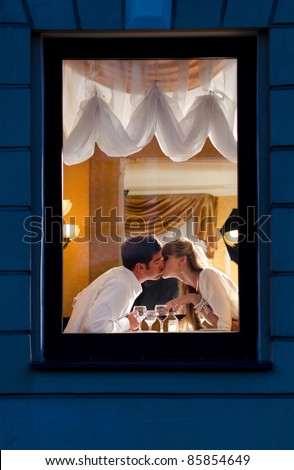 smiling couple is sitting at restaurant, view from street