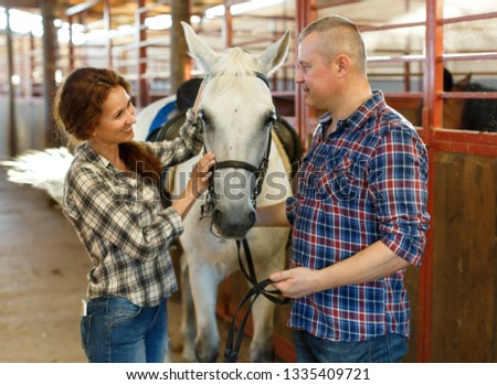 Smiling couple of farmers  standing  with white horse  at stabling indoor