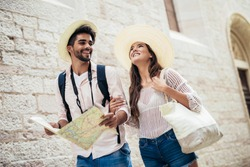Smiling couple of tourists in sunglasses with map in the city - summer holidays, dating and tourism concept