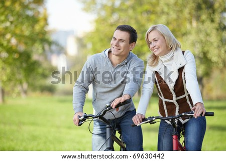 Smiling couple on bicycles in the park