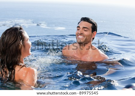 Smiling couple playing in a swimming pool