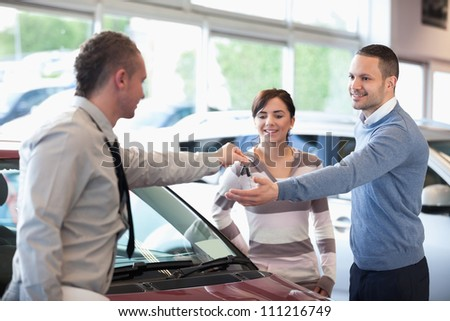 Smiling couple receiving keys from a car dealer in a car shop