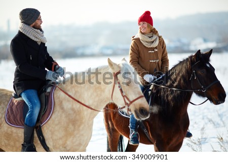 Smiling couple riding on horses outdoors in winter