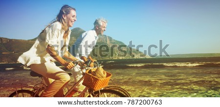Photo of Smiling couple riding their bikes on the beach on a sunny day