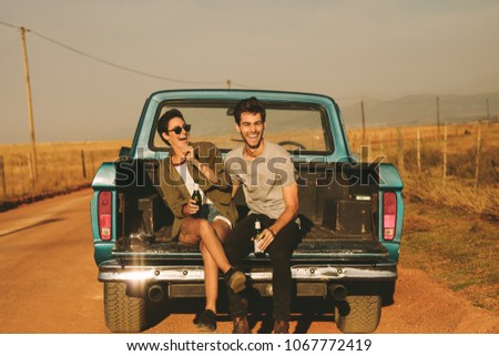 Smiling couple sitting in the back of their pickup truck enjoying the road trip in country side. Man and woman holding a bottle of drink enjoying the road trip.