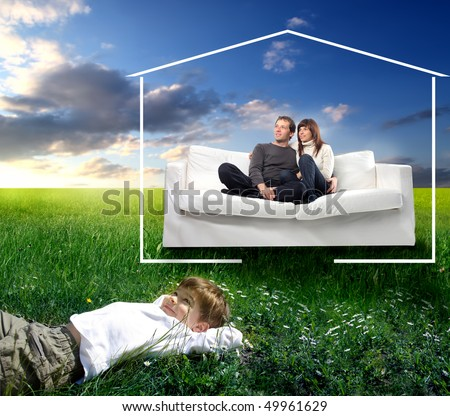 Smiling couple sitting on a couch and happy child lying on green meadow