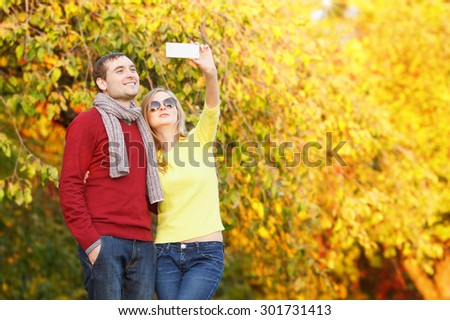 Smiling couple taking selfie with smart phone in the city park. Couple in the autumn garden and taking selfie. Couple taking selfie photo.
