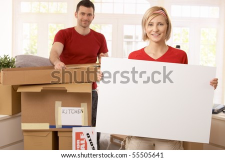 Smiling couple unpacking in new place, copyspace in blank poster.