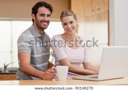 Smiling couple using a notebook while having coffee in their kitchen