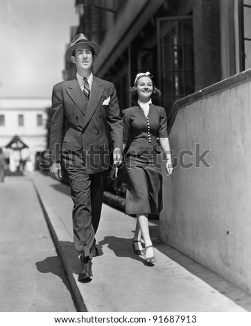 Smiling couple walking on sidewalk