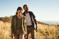Smiling couple walking together down a hillock enjoying the nature. Couple on a hiking trip on a sunny day.