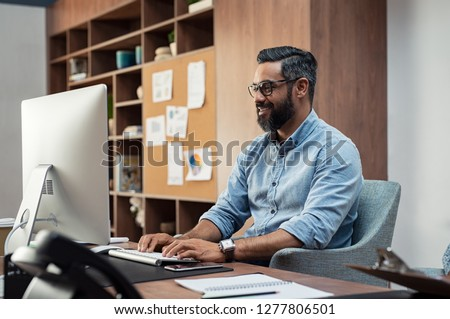 Smiling creative latin business man typing on desktop computer in office. Mature middle eastern businessman working at modern office space. Happy indian man wearing eyeglasses working on his computer.