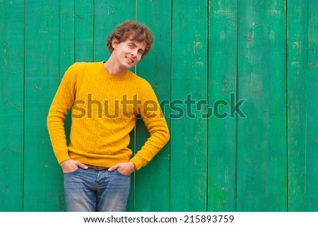 smiling curly man in yellow pullover