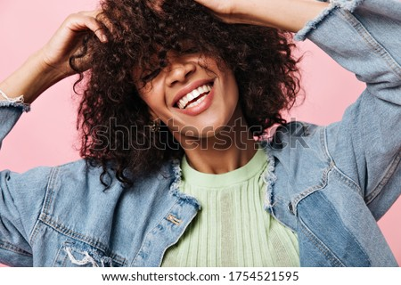 Smiling curly woman in denim jacket posing over pink background. Joyful happy girl in green tee laughing on isolated backdrop