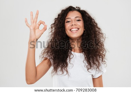 Smiling curly woman showing ok sign and looking at the camera over gray background
