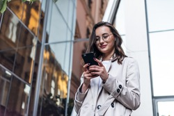 Smiling curly woman wearing trendy sunglasses walks down the central city street and uses her phone. Pretty summer woman in white jacket walks down the street looking at her mobile phone