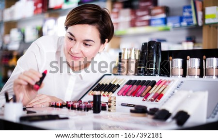 Smiling customer browsing rows of cosmetic products in pharmacy