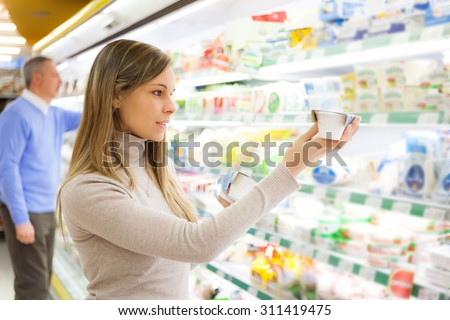 Smiling customer taking a product in a supermarket