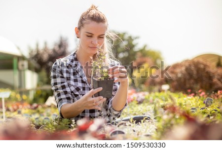 Smiling customer woman in garden center looking for a plants