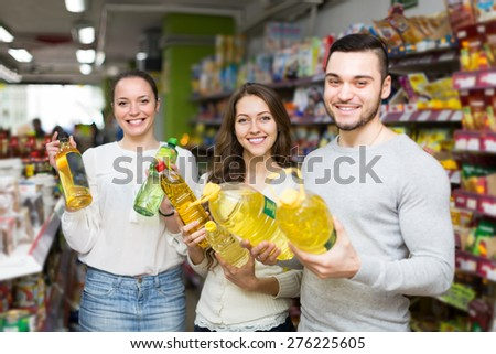 Smiling customers choosing seed-oil in plastic packing at shop. Focus on girl
