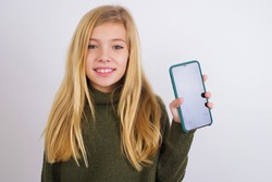 Smiling Cute Caucasian kid girl wearing green knitted sweater against white wall Mock up copy space. Hold mobile phone with blank empty screen