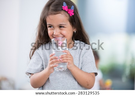 Smiling cute girl holding glass of water at home