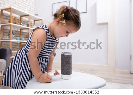 Smiling Cute Girl Looking At Wireless Speaker On White Table At Home #1333814552