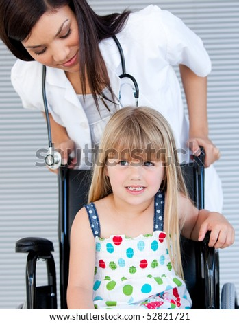 Smiling cute girl sitting on the wheelchair at the hospital