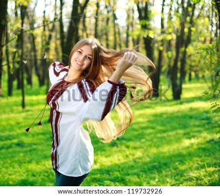Smiling cute girl with long hair dancing in green park